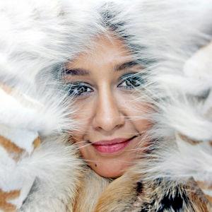 Naisen kasvot näkyvät kettu- ja minkkiturkiksen keskeltä.