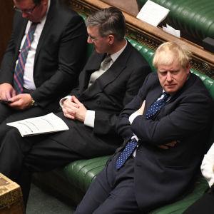Boris Johnson istuu kädet puuskassa parlamentissa.