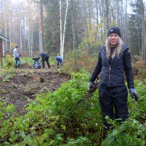 Kvinna röjer i skogsområde.