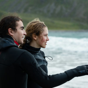 Man och kvinna på kall strand tittar ut mot vattnet.