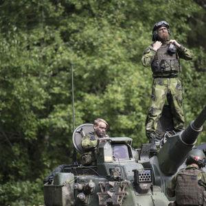 Ruotsalaissotilas seisoo panssarivaunun päällä. Kuvassa kaksi muutakin sotilasta.
