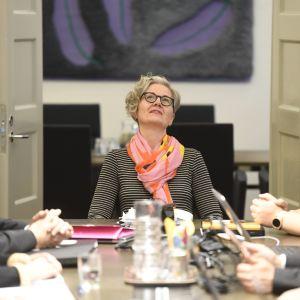 Människor förhandlar runt ett bord. Förhandlingarna leds av Vuokko Piekkala.