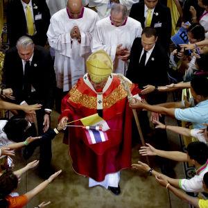 Paavi seurakuntalaisten ympäröimänä.