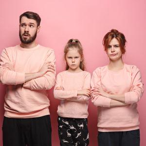 Pappa, mamma och dotter framför rosa fondvägg, alla med korsade armar och sura miner