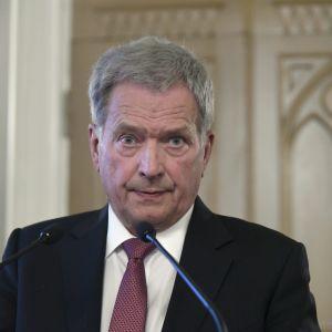 Sauli Niinistö står framför en mikrofon.