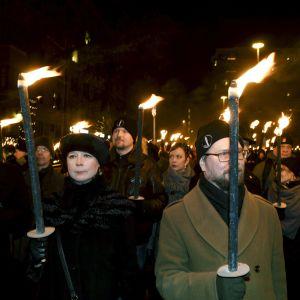 Demonstranter står vinterklädda med facklor i händerna.