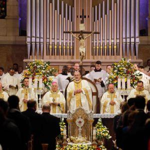 Julmässa i Födelsekyrkan i Betlehem. I mitten står präst och förkunnar under ett kors.