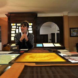 En kvinna sitter bakom ett stort bord täckt av ramar och papper.