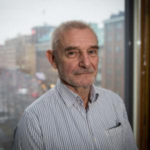 Ralf Sund, en äldre man med kort grått hår och kort grått skägg. Han har en randig skjorta på sig. Han står framför ett fönster med stadsutsikt.