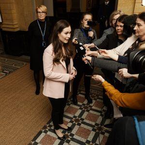 Sanna Marin står i Ständerhusets aula omringad av journalister.