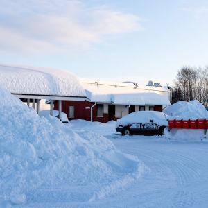 Lumikasoja inarilaisen rivitalon pihalla ja katolla.