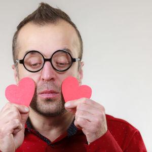 ledsen man i runda glasögon håller upp två pappershjärtan