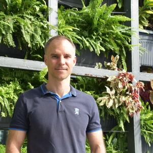 Man i kortärmad skjorta i soligt väder och med en massa gröna växter på hyllor i bakgrunden