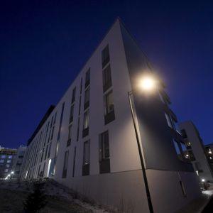 Ett vitt radhus med tre våningar. Det är kväll.