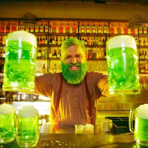 Bartender med grönt skägg och grönt hår håller fram två stop med ilsket grön öl och fler gröna ölsttop står på bardisken.