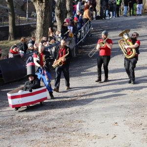 En grupp personer spelar olika blåsinstrument medan de går ner för backen.