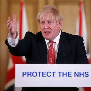 Storbritanniens premiärminister Boris Johnson talar vid ett talarpodium 22.3.2020. Han har sträckt ut högra handen.
