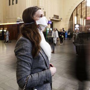 En kvinna står och väntar på någonting på Helsingfors järnvägsstation. Hon har ett vitt munskydd framför munnen och näsan.