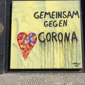 En väggmålning i Berlin med texten tillsammans mot corona