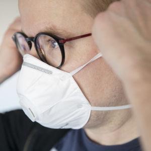 En person justerar sitt andningsskydd vid öronen. Personen har glasögon och en svart tröja på sig och hens ögon är blå.