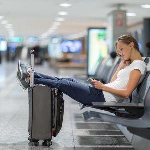 Kvinna sitter tillbakalutad på bänk i en terminal. Hon har fötterna på sin resväska och surfar på sin pekplatta.