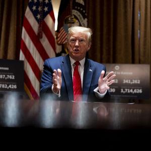 Donald Trump istumassa pöydän ääressä.