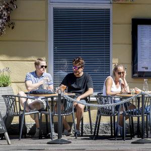 Flera personer sitter på en uteservering en solig sommardag.