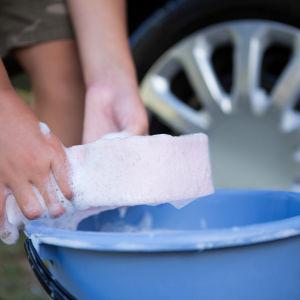 Händer som sköljer tvättsvamp i fat vid ett bilhjul.