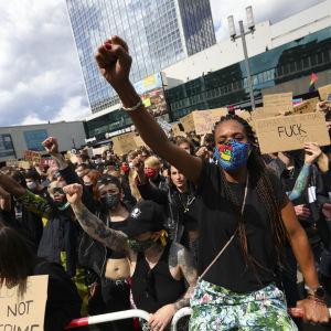 Ihmisjoukko. Etualalla musta nainen käsi nyrkissä kohotettuna.