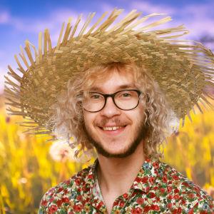 Philip Järvenpää ler in i kameran med en stor stråhatt på huvudet. I bakgrunden syns en sommaräng.