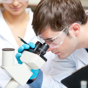 En man i vit rock tittar in i mikroskop.