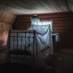 Ullakkohuone, jossa sänky ja muita huonekaluja peitetty vaalealla kankaalla, ikkunasta tulee valoa