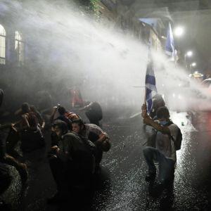 Poliisi ampuu vesitykillä mielenosoitukseen osallistuvia ihmisiä kadulla Israelissa.