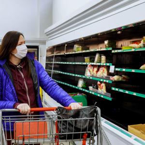 Kvinna shoppar med ansiktsskydd på sig.