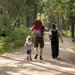 En familj med ryggsäckar på tur i skogen.