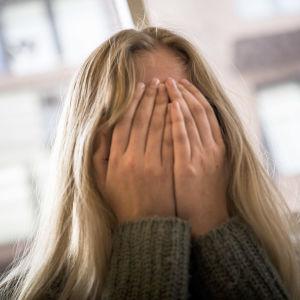 Tyttö peittää käsillään kasvonsa