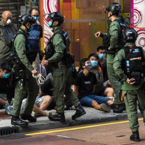 Poliser på gata i Hongkong, på marken sitter unga personer.