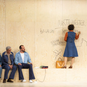En kvinna står på en bänk och skriver på väggen med tusch. Tre personer på sidan av och betraktar henne.