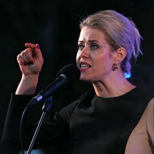 Kvinna med blont hår håller upp fingret medan hon talar.