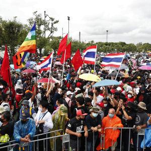 Bild på folkmassa i Thailand. Personerna har paraplyn och regnjackor i muntra färger.
