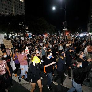 Folkmassa som bär skyltar utomhus när det är mörkt.