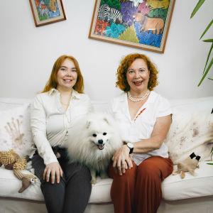 Vivi och Heidi sitter i soffan med hunden som under ett familjeporträtt. Minerna är uppskruvade, stela och påklistrade och tavlor hänger på sned i bakgrunden.