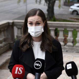 Kvinna i brunt hår och svart kappa och munskydd ser allvarlig ut då hon står framför tre mikrofoner på ständerhusets trappa. Kvinnan är statsminister Sanna Marin.