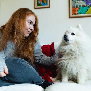 Vivi sitter i soffan och krafsar sin hund.
