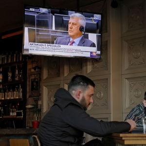 Miehet istuvat baarissa Pristinassa ja Kosovon ex-presidentin oikeudenkäynti on meneillään telkkarissa