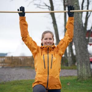 Hanna Kanerva visar pausgymnastik med ett kvastskaft.