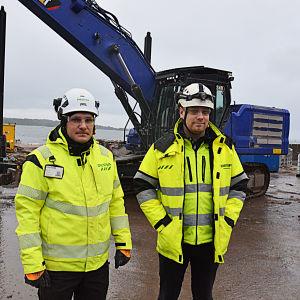 Två byggnadsarbetare står framför en grävmaskin.