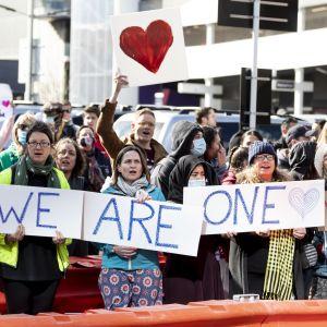 Människor med plakat demonstrerar.