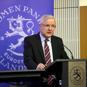 En gråhårig man i kostym talar vid ett podium. Bakom honom en blå plansch med texten Finlands bank och ett lejon.