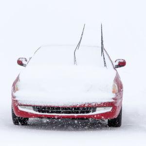 Bil intäckt i snö.